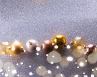 Silver and golden christmas bubbles. Flat lay border on silver background royalty free stock images