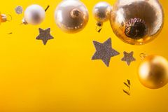 Silver and golden christmas bubbles. And stars on yellow background with copy space stock photography