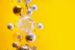 Silver and golden christmas bubbles. And stars flying on yellow background with copy space royalty free stock photos