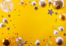 Silver and golden christmas bubbles. And stars flying on yellow background frame with copy space stock images