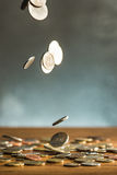 The silver and golden coins and falling coins on wooden background Stock Images