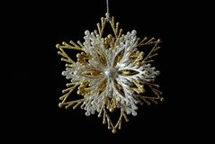 Silver-golden snowflake on black Stock Images