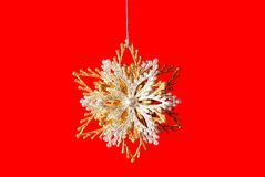 Silver-golden snowflake on pure red Royalty Free Stock Image