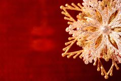 Silver-golden snowflake on red. Silver-golden snowflake on a red blurred background Royalty Free Stock Photography