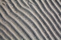 Silver gray sand on sea beach top view close up, ribbed dry sand surface pattern, wavy curved diagonal lines texture royalty free stock images