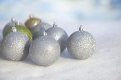 Silver, green and gold Christmas baubles in snow Royalty Free Stock Image