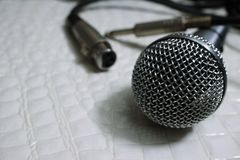 Silver Grille microphone with XLR cable on white leather SELECTIVE FOCUS. Silver Grille microphone mike with XLR cable on white leather SELECTIVE FOCUS royalty free stock photo
