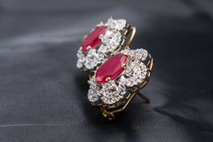 Silver handmade flower shaped earring with a red ruby Royalty Free Stock Images