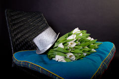Silver hat and white tulips on black chair Royalty Free Stock Photo