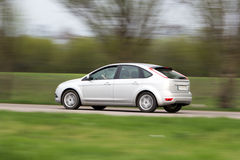 Silver hatchback car in motion blur. Shiny silver modern hatchback car. Side view. Driver's hands on the steering wheel. Green grass, trees and road in motion stock photography