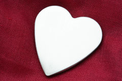 Silver Heart. Silver metal heart against purple material background Royalty Free Stock Photos