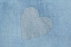 Silver heart on a blue background of cotton fabric. Romantic pas stock photography