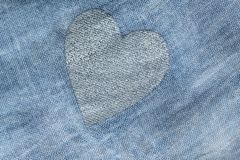 Silver heart on a blue background of cotton fabric. Romantic pas royalty free stock photo