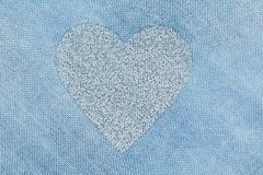 Silver heart on a blue background of cotton fabric. Romantic pas. Tel background. Design with copy space. Denim color. Pastel background Royalty Free Stock Image
