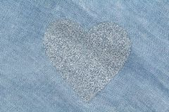 Silver heart on a blue background of cotton fabric. Romantic pastel background. Design with copy space. Denim color royalty free stock images