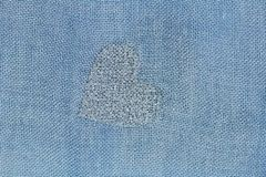 Silver heart on a blue background of cotton fabric. Romantic pastel background. Design with copy space. Denim color stock photography