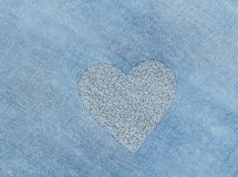 Silver heart on a blue background of cotton fabric. Romantic pastel background. Design with copy space. Denim color. Pastel background stock photos