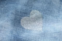 Silver heart on a blue background of cotton fabric. Romantic pastel background. Design with copy space. Denim color royalty free stock photography
