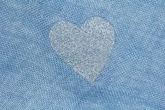 Silver heart on a blue background of cotton fabric. Romantic pastel background. Design with copy space. Denim color stock photos