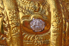 Silver heart in a golden plate representing the Shiva. Hindu temple golden element Royalty Free Stock Photography