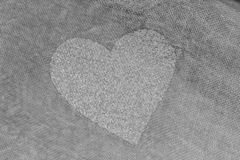 Silver heart on a gray background of cotton fabric. Romantic pas royalty free stock image