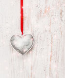 Silver heart  hanging on red cord on white wooden wall , love. Background Stock Images