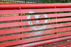 A silver heart painted on a red bench. A silver graffiti heart on a red bench royalty free stock image