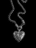 Silver heart pendant on black. Background Royalty Free Stock Images