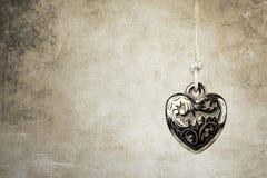 Silver heart pendant. On grunge background Stock Photos