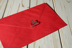 Silver heart pendant on a red envelope Royalty Free Stock Images