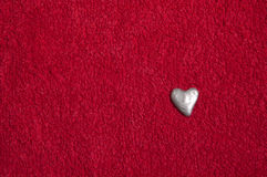 Silver heart on a red fabric. Handmade silver heart on a red fabric background stock photography
