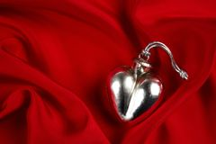 Silver heart on red satin Stock Photo