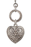 Silver heart on white. Silver heart pendant with ornate design on white background royalty free stock image