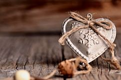 Silver heart on a wooden table with decorations. Valentines day. Love. Gift. Ilustration on a natural background. Silver heart on a wooden table with Stock Photography