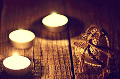 Silver heart on a wooden table with decorations. Valentines day. Love. Gift. Ilustration on a natural background. Candles and fire. Silver heart on a wooden Royalty Free Stock Photo