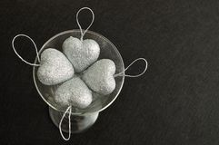 Silver hearts in a glass. Valentines day. Silver hearts in a glass isolated against a black background. Top view stock photo