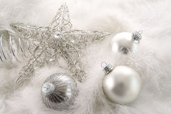 Silver holiday ornaments in feathers Stock Photo