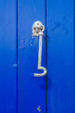 Silver hook on blue wooden door, practical decorative element, v stock images