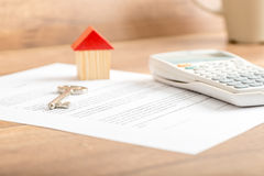 Silver house key lying on a contract for house sale Royalty Free Stock Photography