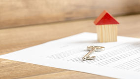 Silver house key lying on a contract of house sale Royalty Free Stock Image