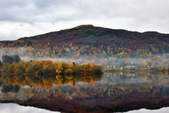 Silver Howe & Grasmere in Autumn. Still water on Grasmere with reflections of Autumn colours and Siver Howe Royalty Free Stock Image