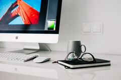 Silver Imac Turned on Beside Gray Ceramic Mug and Black Frame Eyeglasses Stock Photography