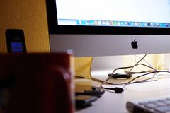 Silver Imac Turned on Beside Red Ceramic Cup Royalty Free Stock Photography