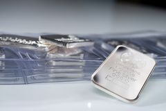 Silver ingot weighing one troy ounce. Against the backdrop of many packaged bars stock photography