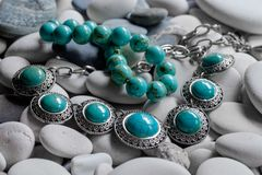 Silver jewelry on pebbles royalty free stock photos