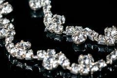 Silver jewelry with diamonds on a black background.  Royalty Free Stock Photography