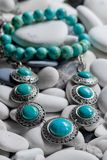 Silver jewelry on pebbles royalty free stock photography