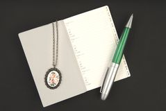 Silver jewelry, pen and notebook Stock Photos