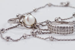Silver jewelry: ring, earrings and chain. Silver ring with precious stones and pearl are together with a silver chain on acrylic Stock Photo