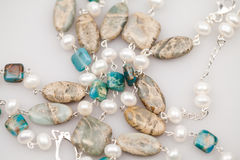 Silver jewels with colorful precious stones. And light grey background Royalty Free Stock Image